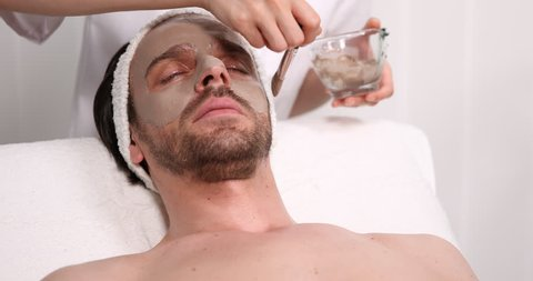 Beautician Applying Sea Mud Mask on Man Face Patient Lying Resting in Spa Clinic