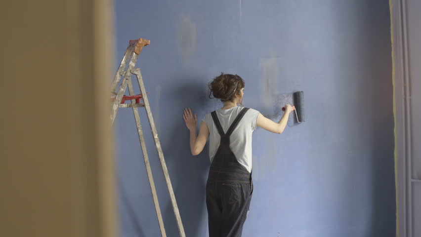 Girl painting blue wall  with roller | Shutterstock HD Video #34594405