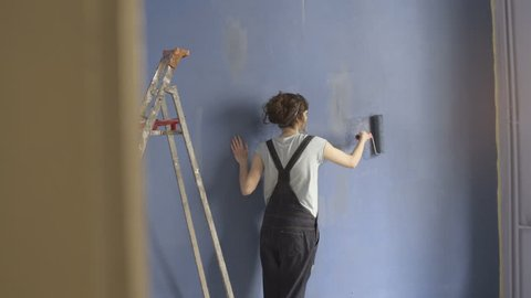 Girl painting blue wall  with roller