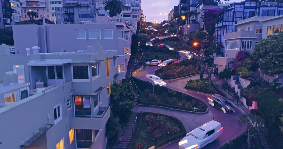 Aerial drone boom down of cars driving down the winding road of Lombard Street at night with streaky car lights. In the background is the San Francisco Skyline with a view to the Bay Bridge | Shutterstock HD Video #34604245