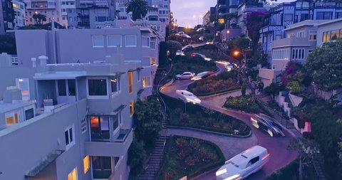 Aerial drone boom down of cars driving down the winding road of Lombard Street at night with streaky car lights. In the background is the San Francisco Skyline with a view to the Bay Bridge
