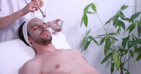 Cosmetician Apply Mineral Mask on Customer Man Face Patient Rest in Beauty Spa