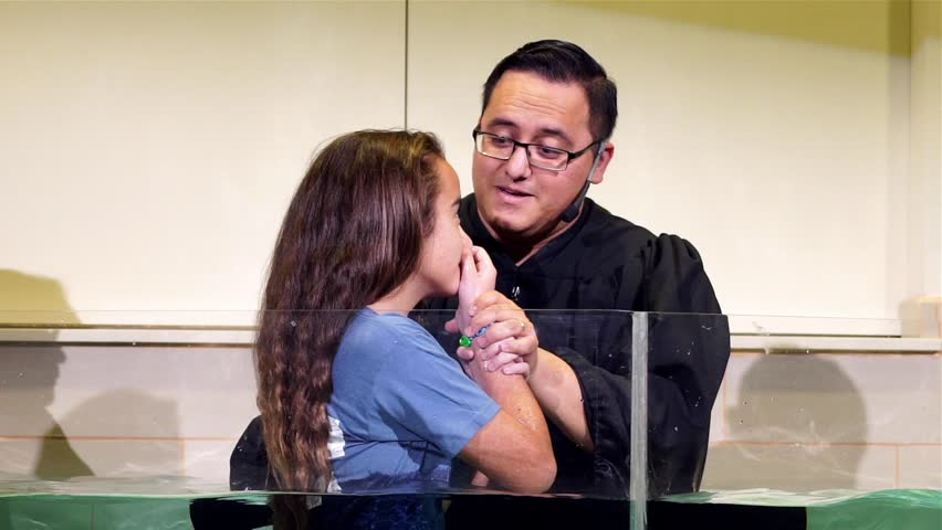 Shepherd Church, Los Angeles, California, USA, January 7, 2017: A pastor baptize a girl.Slow motion. Baptism is a Christian sacrament of admission and adoption.