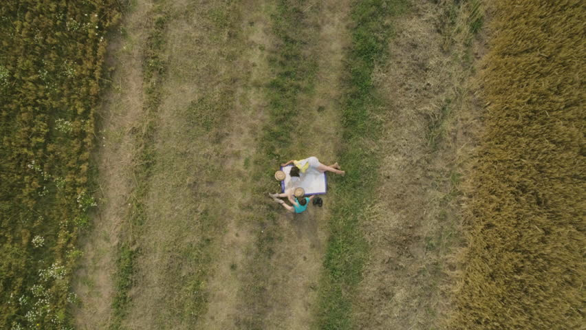 Young little cute girls Playing explorers with Map of Italy reading and pointing in green wheat Field slow motion drone top aerial view
