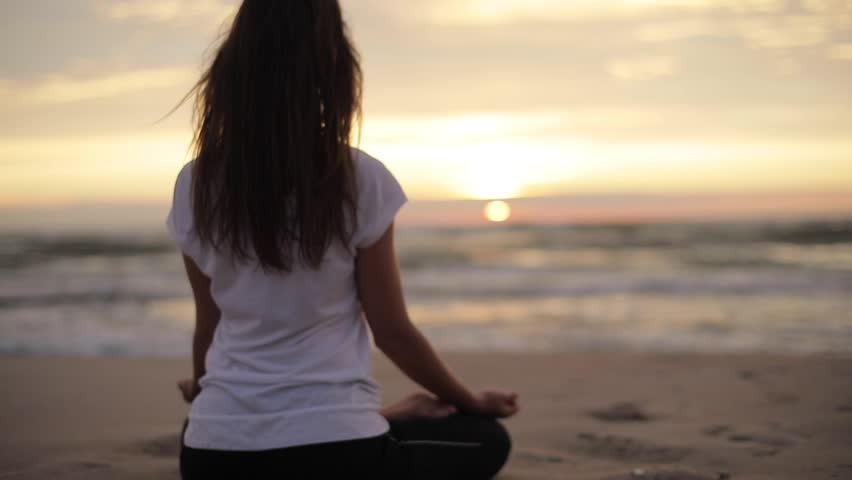 Woman meditates in lotus pose on sea sand sunset evening close up slow motion. Back view of no face female silhouetted sits in Buddha meditation position near ocean shore with waves rolling over