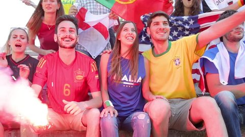 Happy supporters from different countries together at stadium. Fans from multiple countries enjoying a match together. Sport, respect and fair play concepts