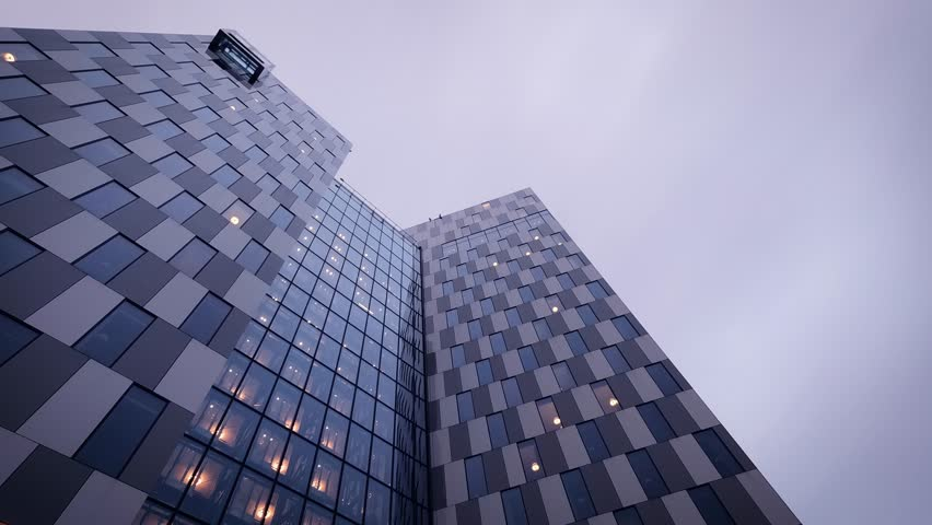 Cinematic time lapse of Clarion hotel building facade. Cloudy day turning to night at Helsinki. Sky, building facades and elevators moving fast while camera filming up wards. Finland
