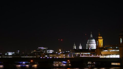 Night city skyline of London. St Paul's Cathedral, the River Thames and the Southeastern train crossing the river and entering the station.