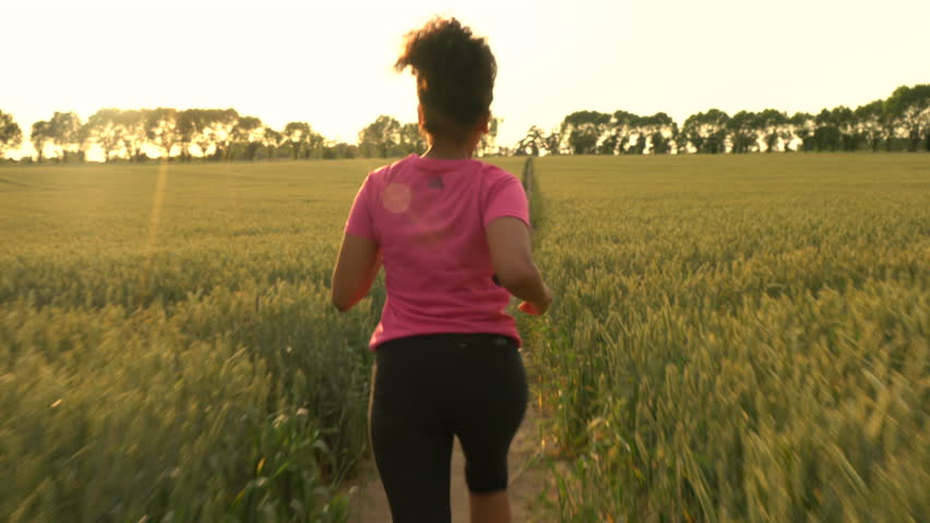 4K video clip of beautiful healthy mixed race African American girl teenager female young woman runner running on path through field of barley or wheat crops at sunset