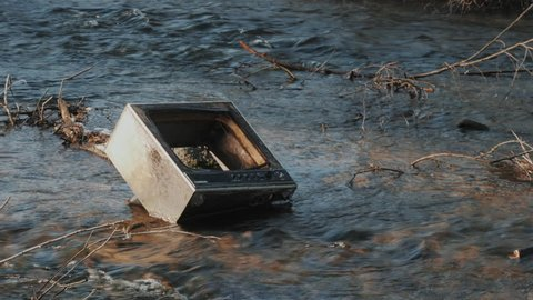 Old retro TV in the river after the flood. The debris from the houses. Pollution of the environment, ecology.