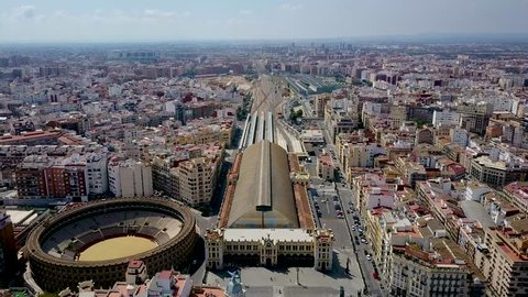 Slow upward panning aerial drone footage of Valencia Spain and the train station and Colosseum