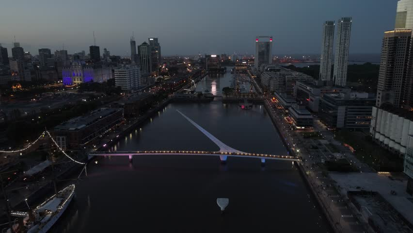 4k Aerial Drone Scene Of Puerto Madero Harbor-Puente de la Mujer Footbridge-City Buildings Night Lights-Buenos Aires at Sunset-Argentina-Ciudad de Buenos Aires at Sunset.