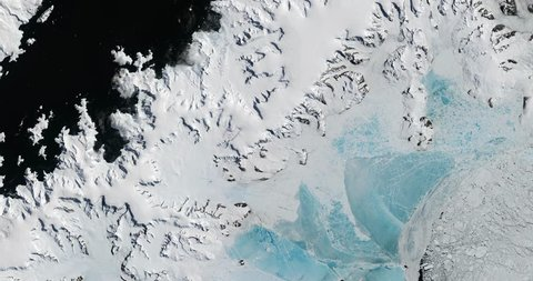 Very high-altitude overflight aerial of Antarctic glaciers, ice sheets, nunataks and sea ice. Clip loops and is reversible. Elements of this image furnished by NASA