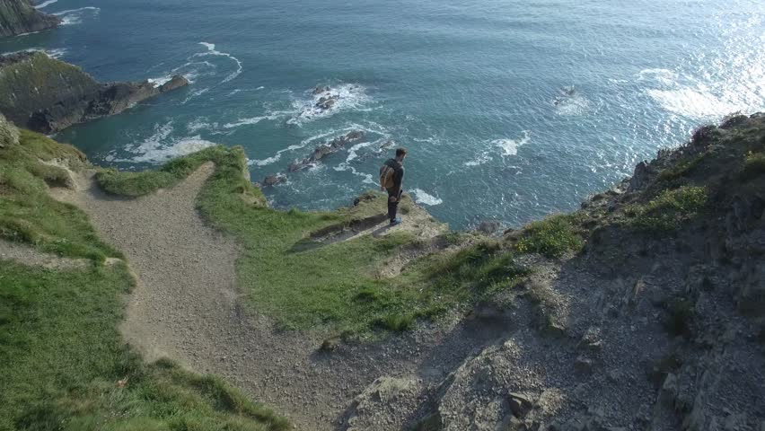 Aerial view of man with backpack on top of a cliff in front of the ocean - Old Head of Kinsale, Ireland | Shutterstock HD Video #34715875
