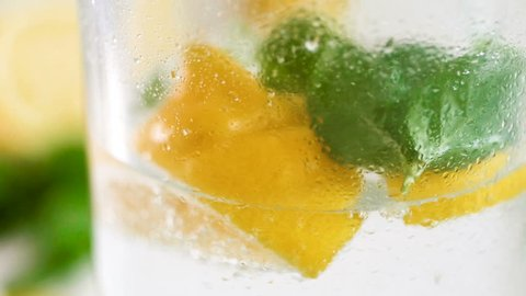 Closeup slow motion motion video of pouring water and throwing ice cubes in glass of lemonade