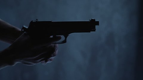 Man with 9 mm handgun takes a shot. Shot from above with an angle