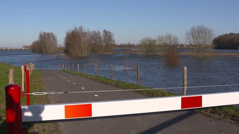 road barrier, flooded road due to the rising water level of the river IJssel. VEESSEN, THE NETHERLANDS - JANUARY 7, 2018