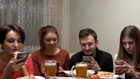 Cinemagraph - Young men sitting at sofa and using their phones. Friend is boring. Group of friends at dinner party with all people on the table occupied with cellphones.