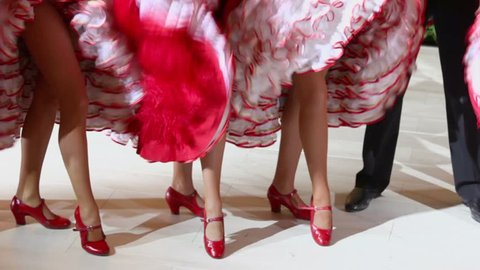 Cancan dancers stand and shake dresses near men in black pants, closeup view with only legs visible