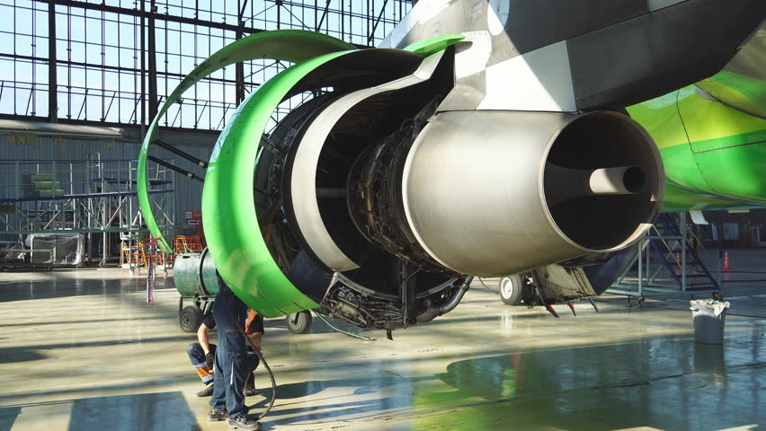 EEngine and chassis of the passenger airplane under heavy maintenance. Engineer checks the aircraft engine. Aircraft repair in the hangar. Aircraft maintenance. Aircraft building. Start the jet engine