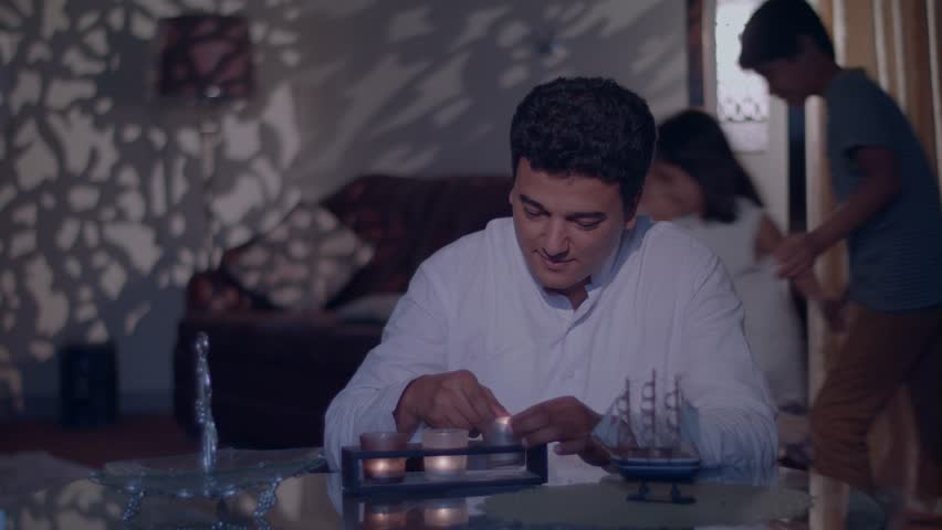 Children move secretly as their father lights up candles for Eid festival