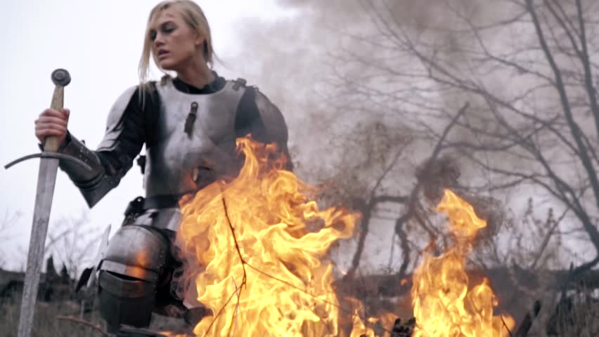 Wounded Jeanne d'Arc is kneeling by the fire