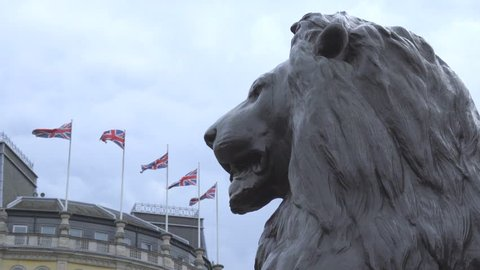Low static view of bronze lions and flags near Trafalgar