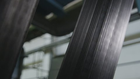 closeup rubber tire flat bar moves to machine tool during production process in manufacturing factory