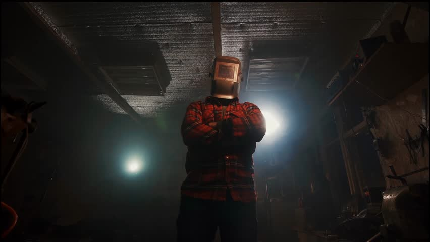 portrait of a man with crossed arms in the welding mask in the home garage