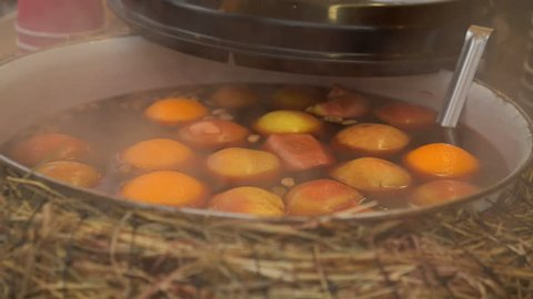 Mulled wine in a saucepan with apples and oranges. Hot drink. Fruit drink. Food fair. Street food.