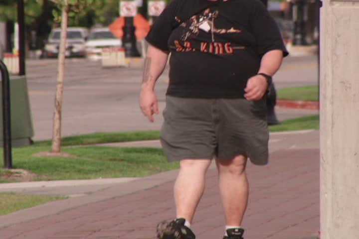An overweight man walking down urban street.