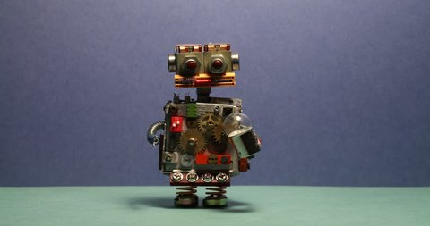 Funny robot serviceman walks and waving his arms. Toy cyborg with light bulb. Blue wall green floor background.