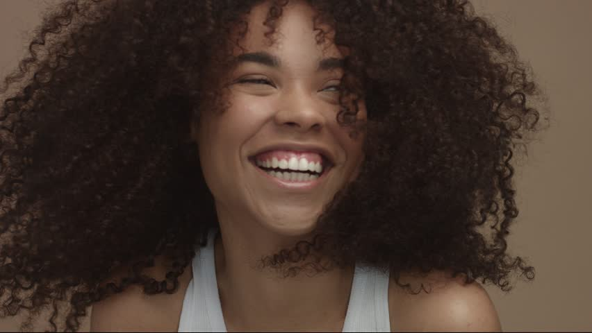 happy laughing black woman with wind moving her cyrly hair in sytdio