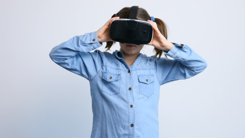 Cute young girl wearing VR virtual reality headset over a gray background playing a 360 degrees game | Shutterstock HD Video #34855765