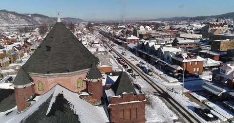 A daytime winter forward aerial establishing shot of a quiet small town's residential neighborhood after a fresh snowfall. Pittsburgh suburbs.