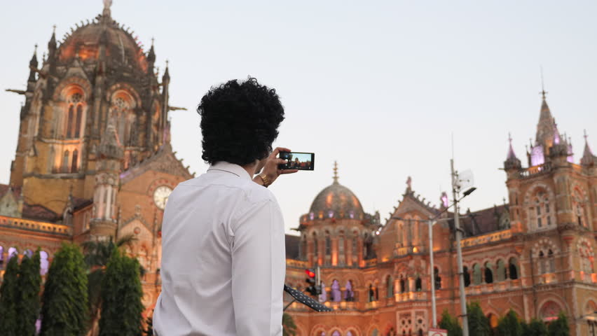 4k footage of office going young man using mobile phone, tablet, laptop in front of CST previously Victoria Terminus. | Shutterstock HD Video #34867555