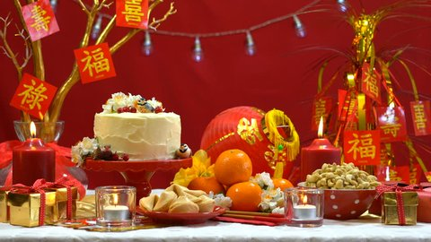 4k Chinese New Year party table in red and gold theme with food and traditional decorations