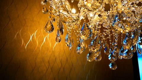 slow moving of Brilliant crystal chandelier hanging on ceiling with filter color effect  in a luxurious interior