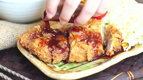 Japanese food : Tonkatsu is deep fried pork Japanese style. Served with bbq sauce, vegetables and steamed rice.