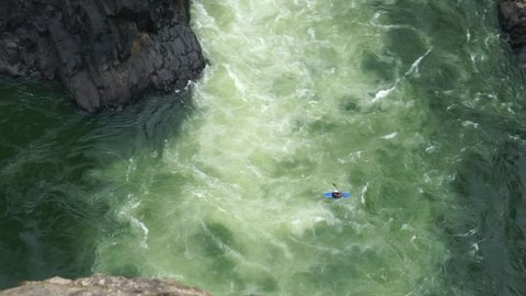 A man is with his kayak in the wild Zambezi river underneath the Victoria falls