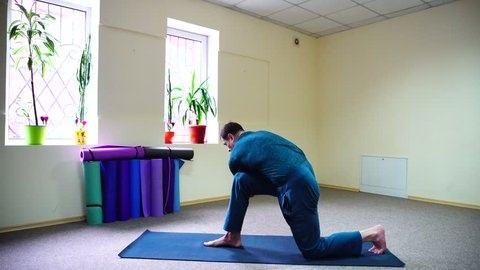 Beautiful dark-haired man performs asanas from yoga, guy sitting in room on floor on fitness mat. Inside spacious and bright, walls painted in nice yellow color, on windowsills pots with flowers