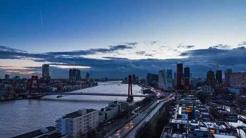 Beautiful timelapse of the skyline of Rotterdam, the Netherlands, with the river Maas and the Erasmus bridge at sunset