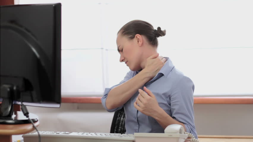 Young woman suffering from neck pain while working on computer