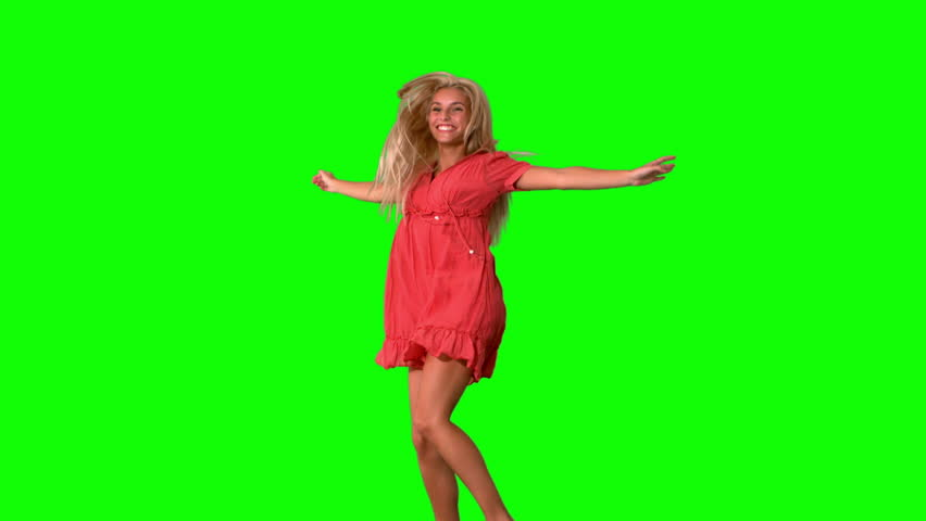 Attractive blonde jumping on green screen in slow motion