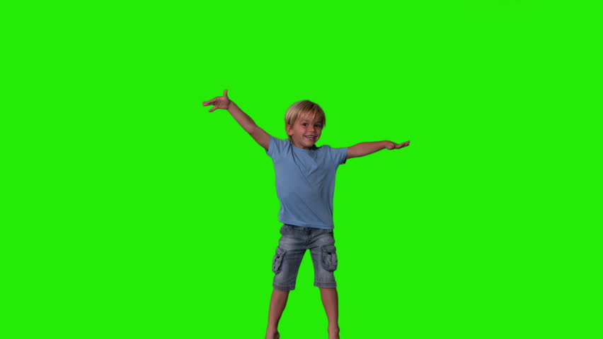 Boy in denim shorts jumping on green screen in slow motion #3496595