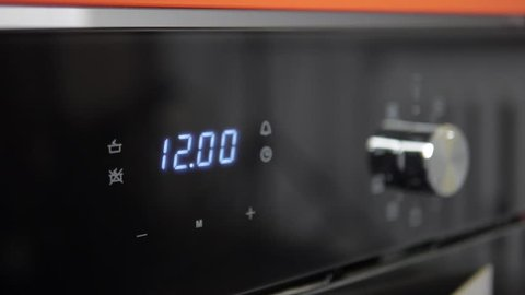 Metallic Toggle Switch of the Cooker Oven. Close-up View. Digital Clock of oven. Front panel of modern black glass oven, red indicators, new shiny buttons. Modern design in details.