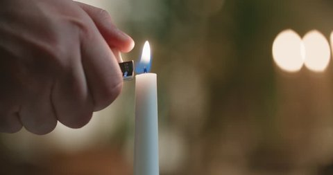 close-up of a man's hand lighting a candle