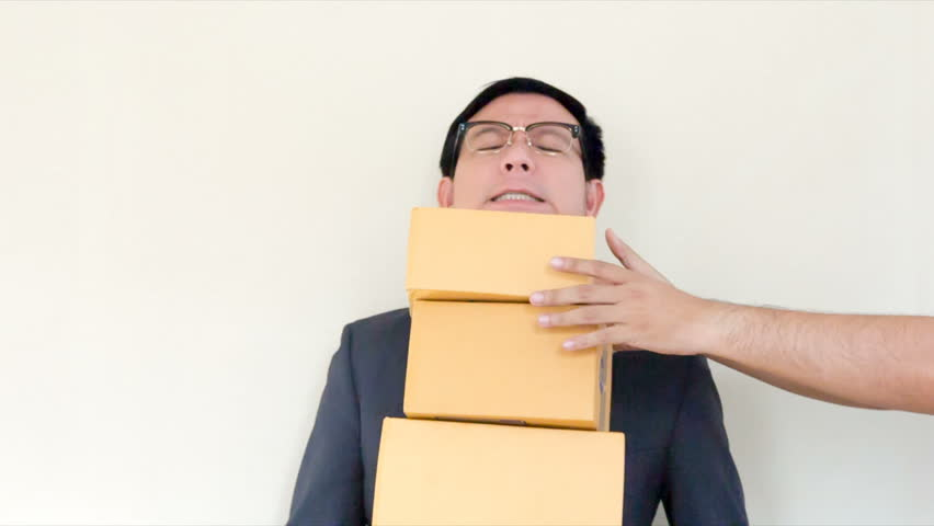 Asian male business man dressed in a suit and glasses. Stand by the box to increase the number of boxes so that he can not get any weight more.