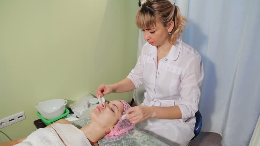The beautician cleanses the skin with a sponge. Woman is lying on a couch spa salon. Woman receiving spa treatment | Shutterstock HD Video #35006965