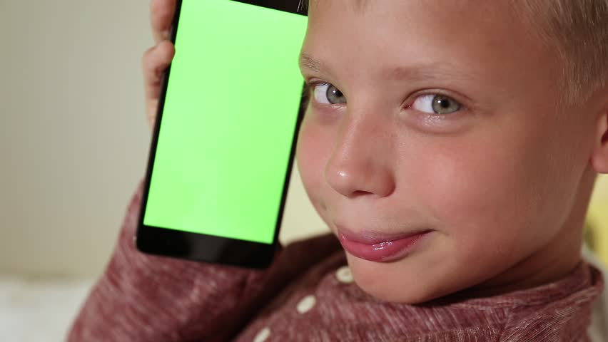 Mockup video of cute funny smiling kid sitting in home interior. Closeup profile portrait of child holds modern mobile phone with blank green screen in hand near face. Real time full hd video footage. | Shutterstock HD Video #35009365